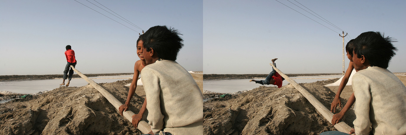Anjar, Gujarat, 2005: Children of migrant salt-pan workers family play on a makeshift see-saw at the work site.
