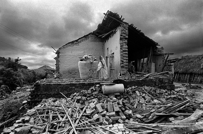 Madhubani, Bihar. 1988: A victim of the earthquake stands in her destroyed home.