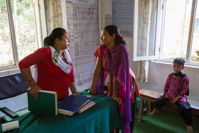 Tanka Kumari with health volunteer Anita Rajbansi at Sitalapati Health Post, Sindhuli district, Nepal, 2015. Sitting on bench is Tanka Kumari's daughter, Sita.