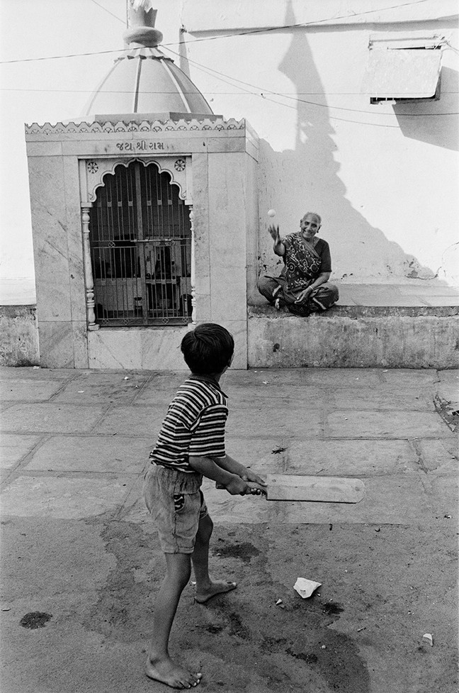 A Hindu woman, sitting beside one of the numerous new Ram temples in  Vanmadi Vanka Ni Pol, plays cricket with her gradson during curfew.