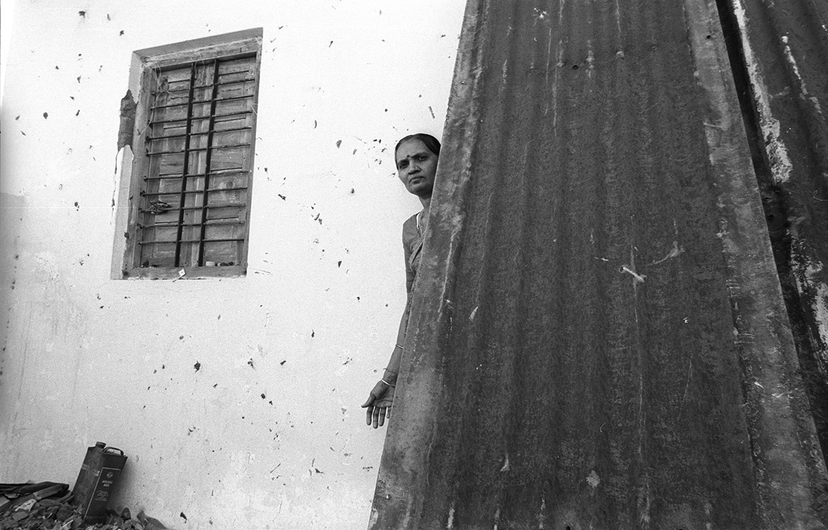 Gitabehn peeps out from behind tin sheets that protecs her 2nd floor home in  Vanmadi Vanka Ni Pol from incoming stones and petrol bombs.