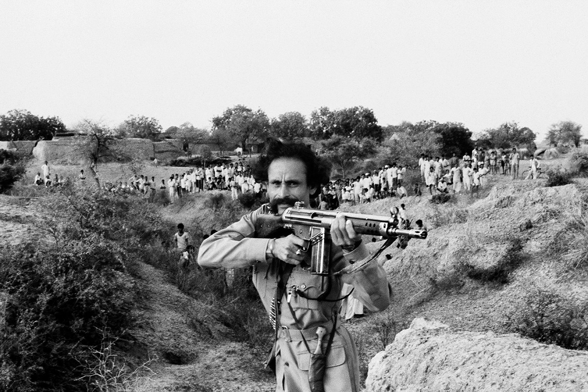 Malkhan Singh showing off his rifle to assembled villagers in the ravines outside Madanpura village on the day of his surrender, 1982.