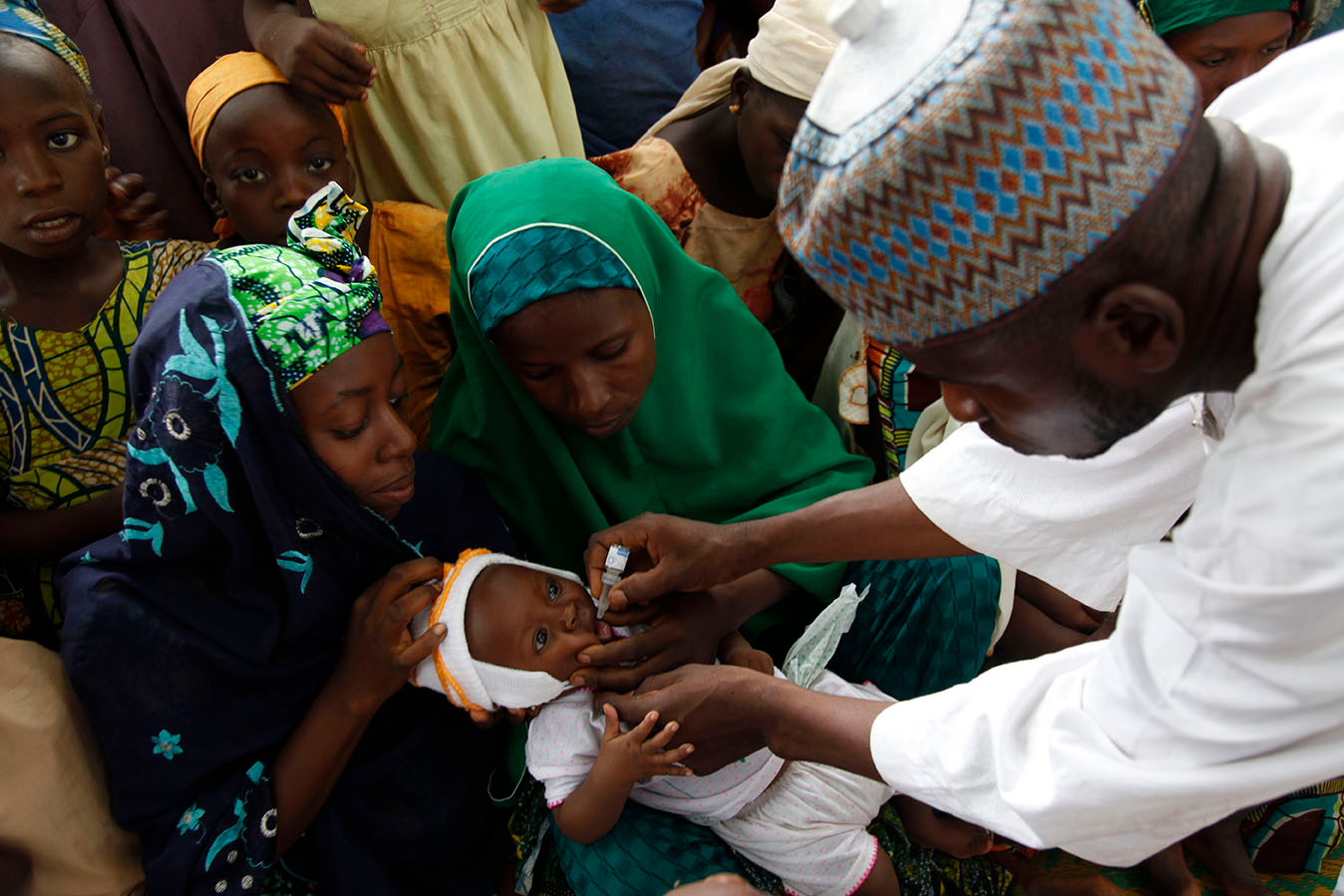 Children receive Oral Polio Vaccine during the official flag-off of the polio campaign of the Gwale LGA at Tudunyola in the Kabuga locality of Kano city, Nigeria, 2010.
