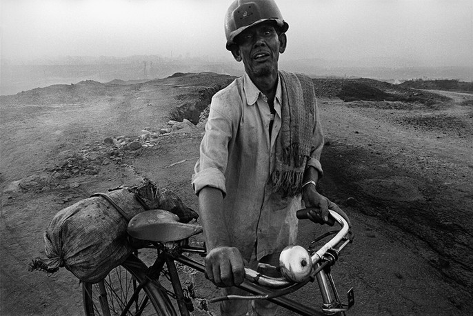 Jharia, Jharkhand. 1999: After a night-shift, a coalminer returns home through the Lodna Fire Area. The Jharia coal mines area has been smouldering with underground mine fires for several decades now.