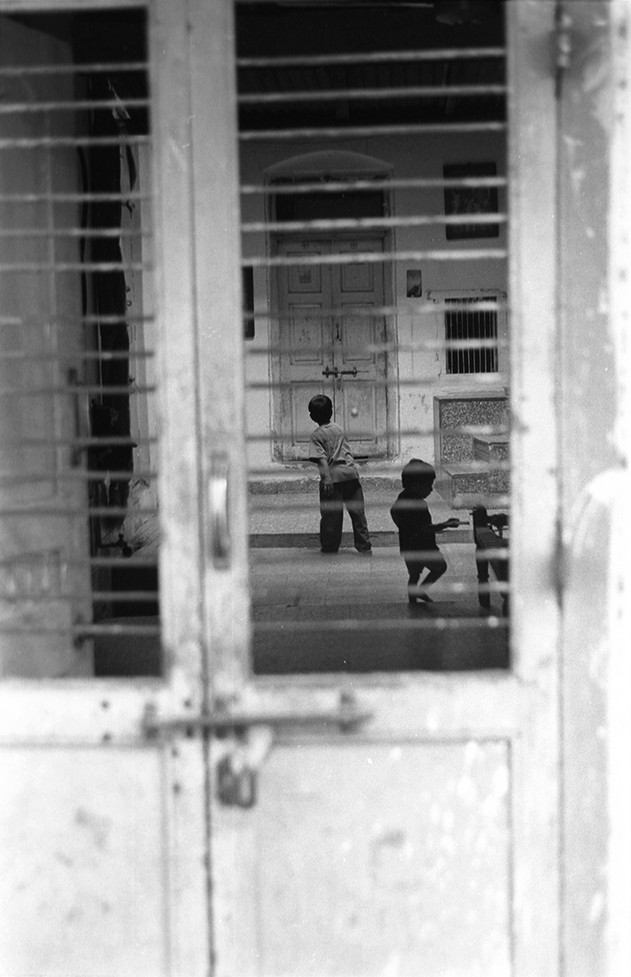 Children playing behind closed doors during curfew in the Hindu locality Vanmadi Vanka Ni Pol.