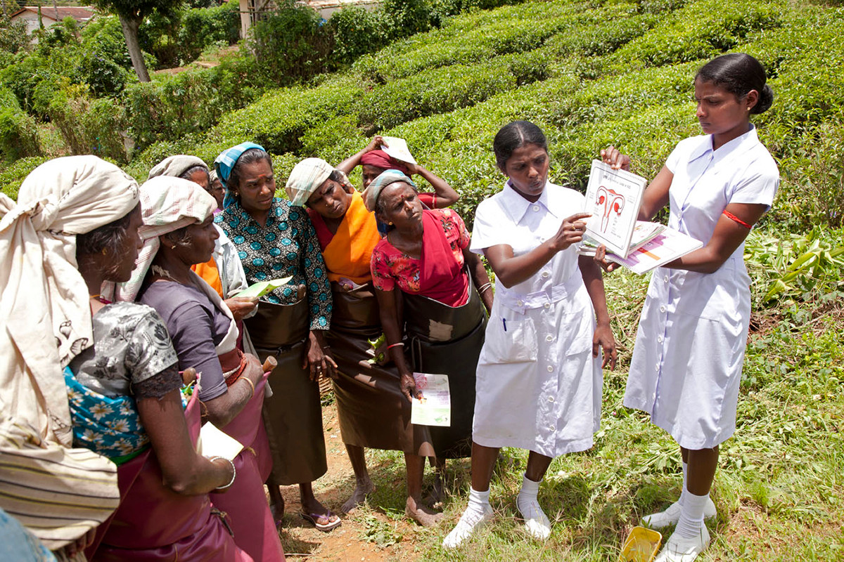 FPA volunteers attached to the government health system interact with women tea pluckers at a tea garden during their lunch break to mobilise them to attend government health clinics at Kotiyagalla Tea Estate, Nuwara Eliya, Sri Lanka, 2012.