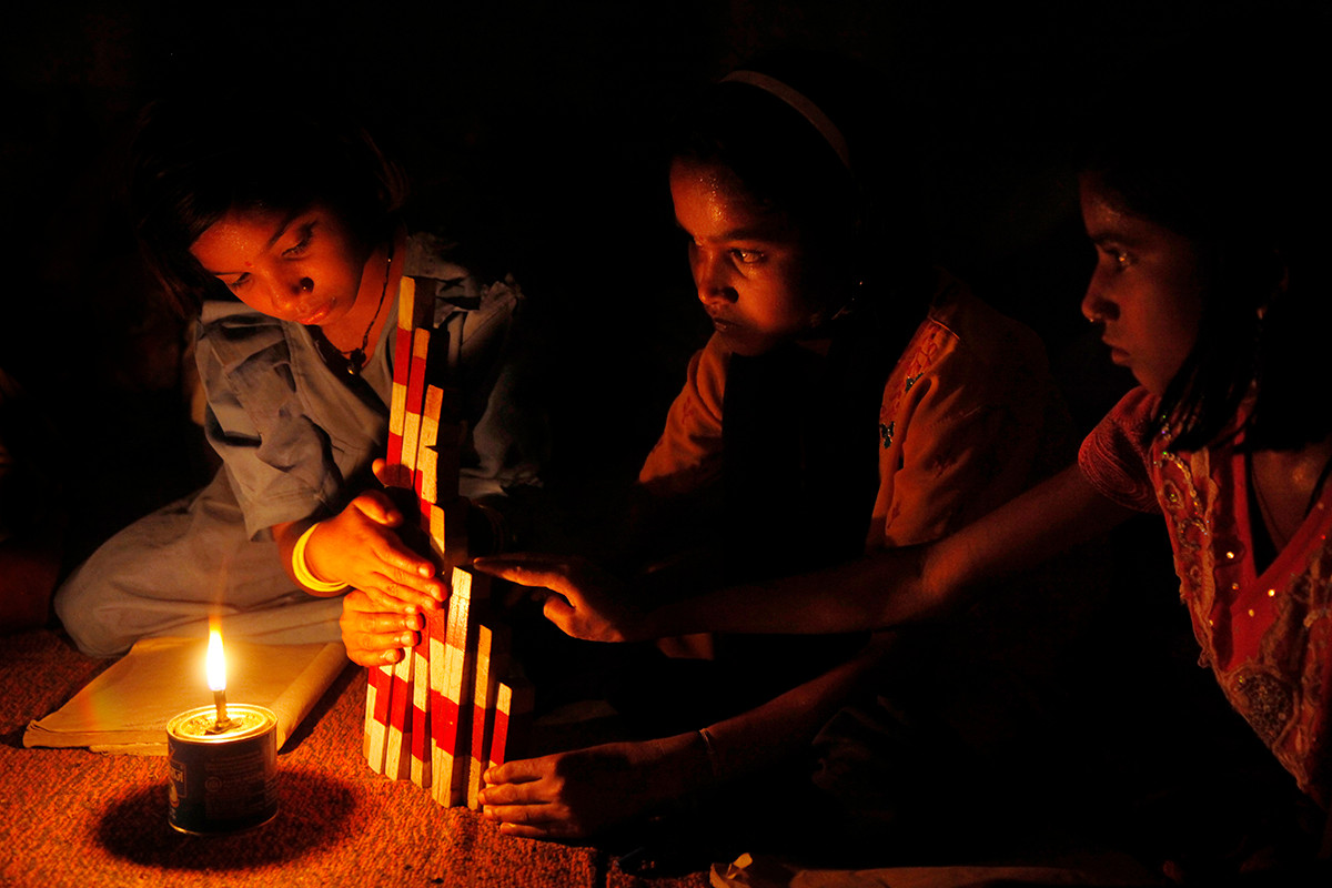 Nuapada district, Orissa, 2009: Students study by lamplight while using TLMs in the evening at the Dongariguda Residential Care Centre.