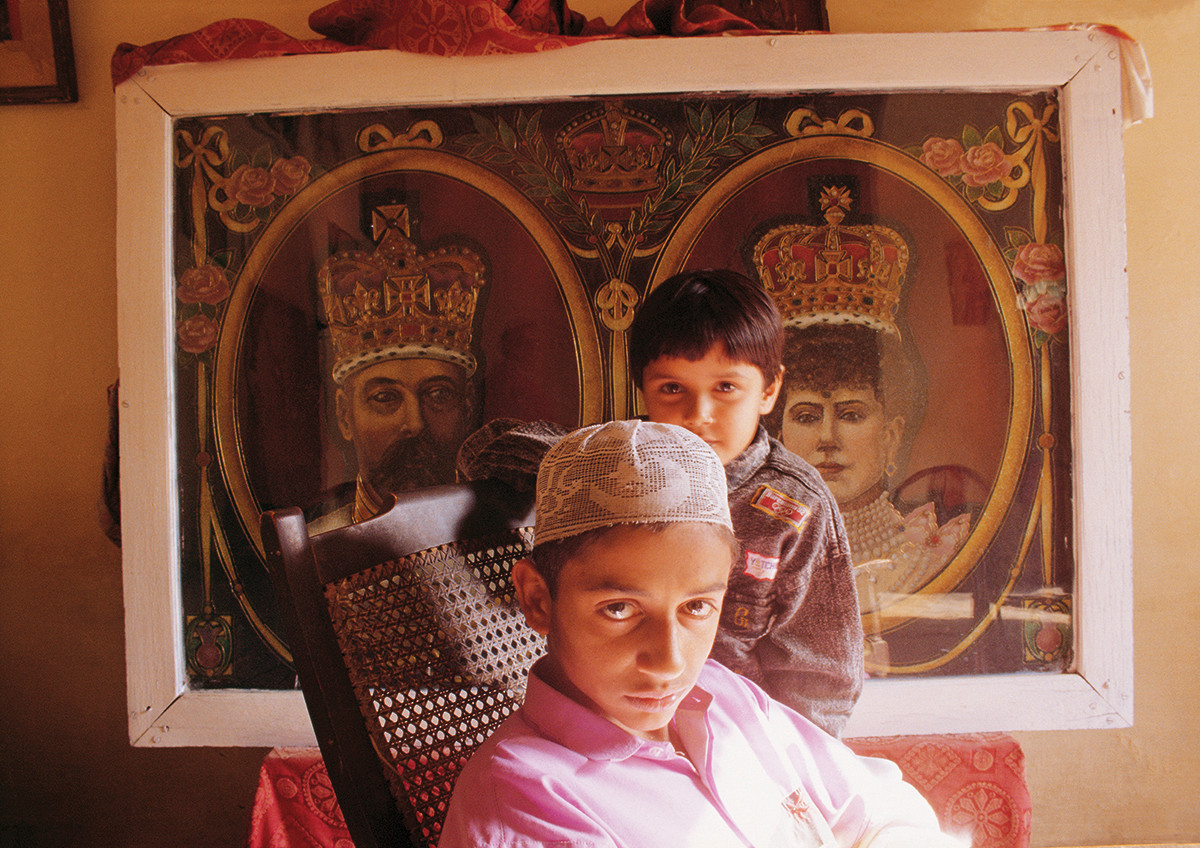 Malerkotla, Punjab. 1994: Sajid Ali, the adopted son of the Begum of Malerkotla, with his real sister Rabiya, sits in front of portraits of King George V and the Queen of England at the palace.
