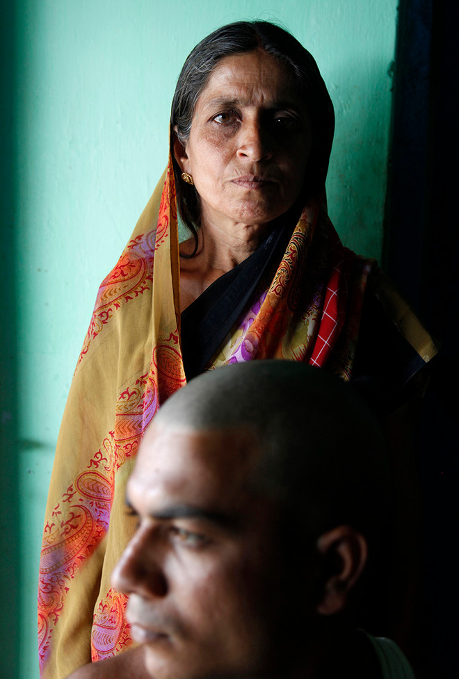 Pramila, wife of Pritilal Thakre, a farmer from Dongrala village who committed suicide, with her son, Pramod, in their home.