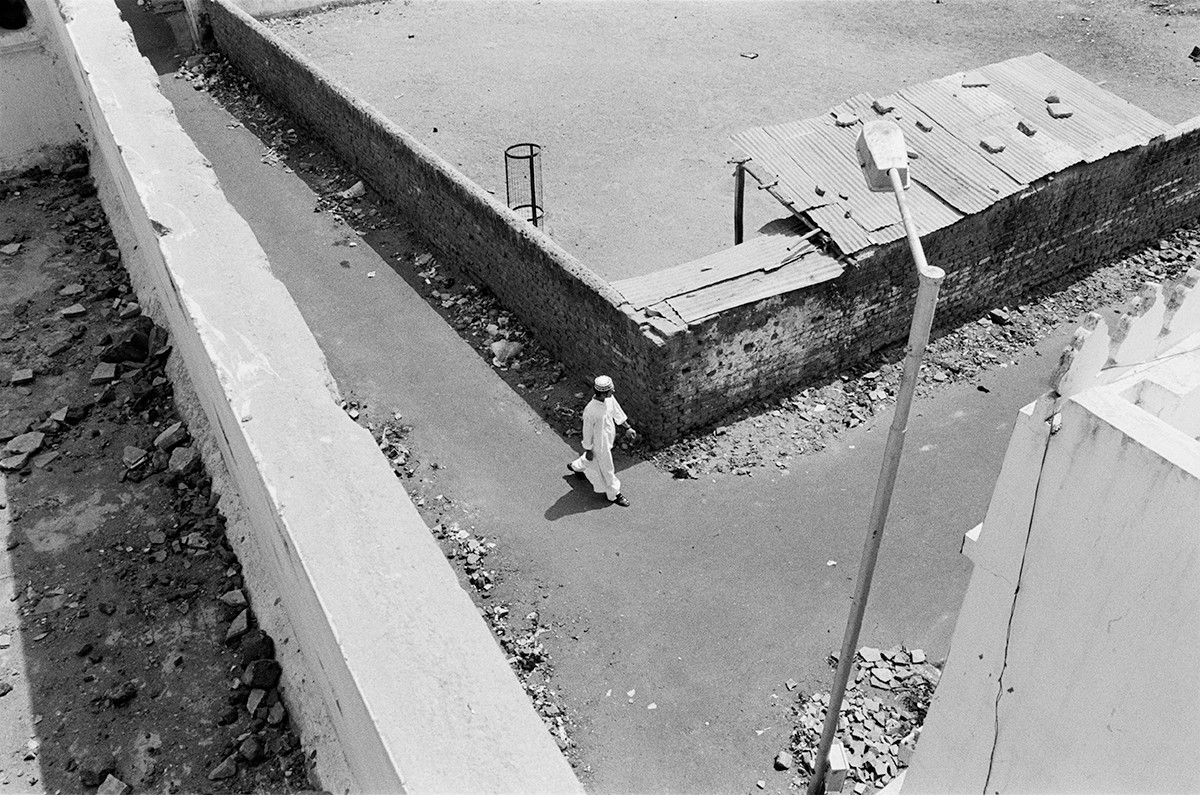 A Muslim youth is seen from the roof of a Hindu home as he walks along the Wall  to the mosque in Jilaiwada.