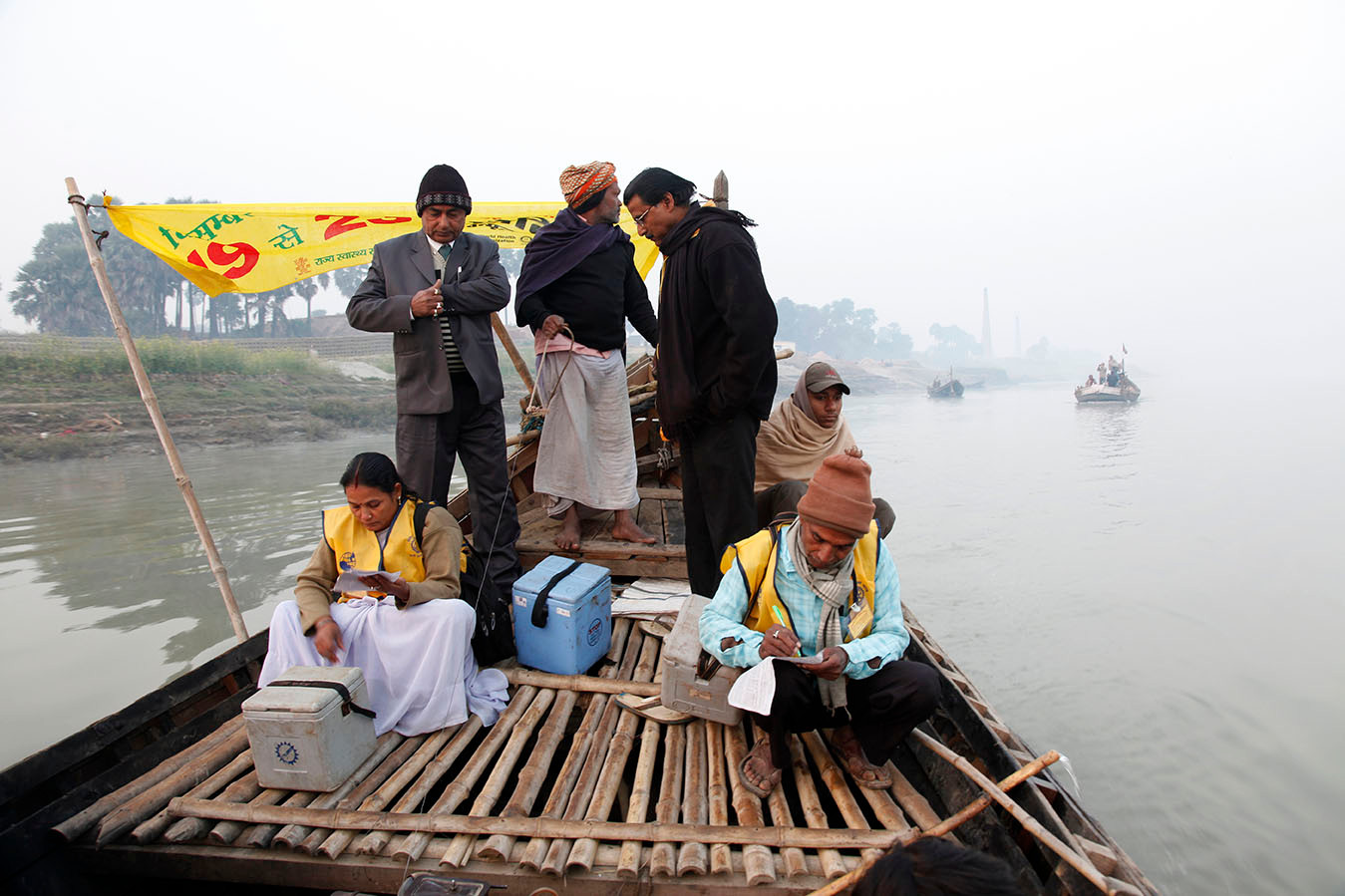 Polio vaccination team members travel in a boat to cross the Ganges river to their area of work in Kala Diara, Bihar, India, 2010.