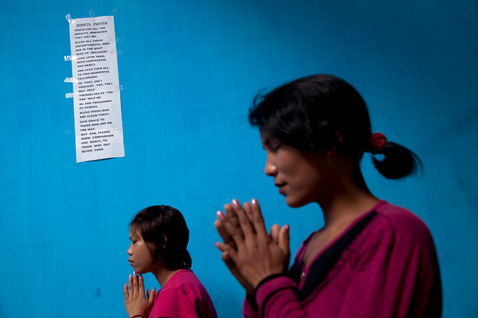 Residents Lulun and Ngaikim  pray in front of a Addicts Prayer pasted on the wall at the Leimasinloisang Short Stay Home for re-integration of rehabilitated Female Injecting Drug Users in Imphal, Manipur, India, 2011.