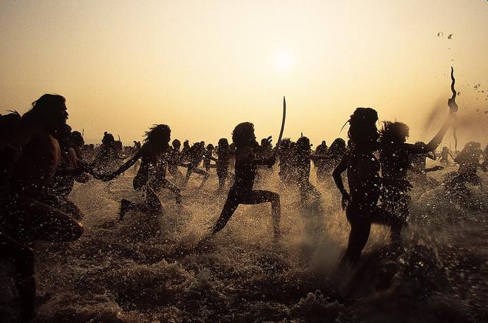 Allahabad, Uttar Pradesh. 2001: Naga Sadhus charge into the holy waters for the auspicious bath during the Mahakumbh Mela.