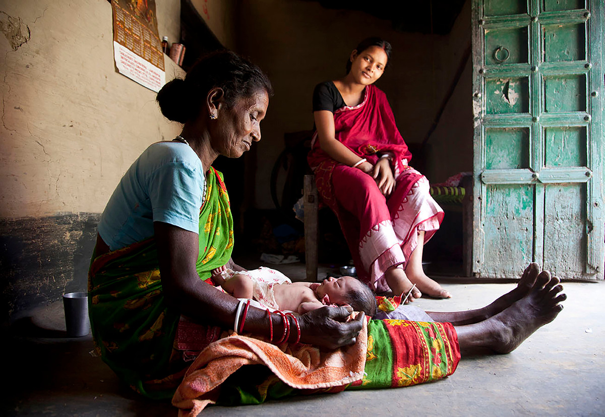 AIF MANSI beneficiariy Balika Mahto's 1-day old child is looked after by a traditional birth attendant Manjura Kalindi in Bordih village, Seraikela district, Jharkhand, India, 2012.