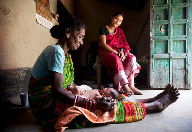 AIF MANSI beneficiariy Balika Mahto's 1-day old child is looked after by a traditional birth attendant Manjura Kalindi in Bordih village, Seraikela district, Jharkhand, India, 2012.