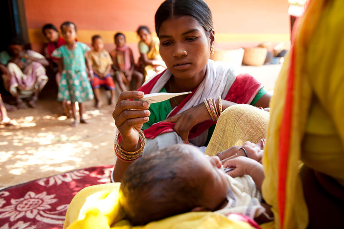 Sombari Soren, a Sahiya under the MANSI program supported by American India Foundation, takes the temperature of the newborn child of Mukhi Soren in their home in Poradih village, Seraikela district, Jharkhand, India, 2012.