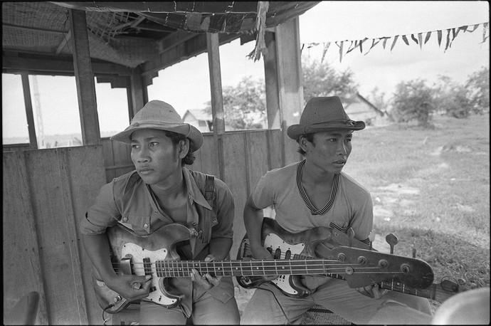 Militiamen at a checkpost play guitars.