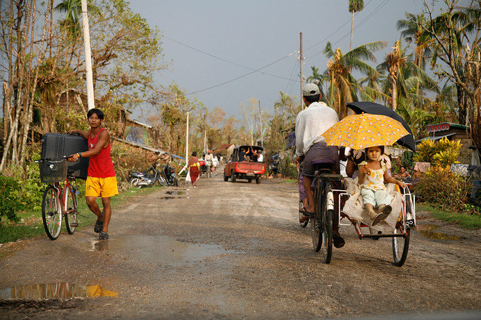 A child with a parasol rides in a pedicab while a young boy carries his belongings in a suitcase in Kyaiklat town damaged by Cyclone Nargis, on the road to Bogalay, in the Irrawaddy Division of Myanmar (Burma).