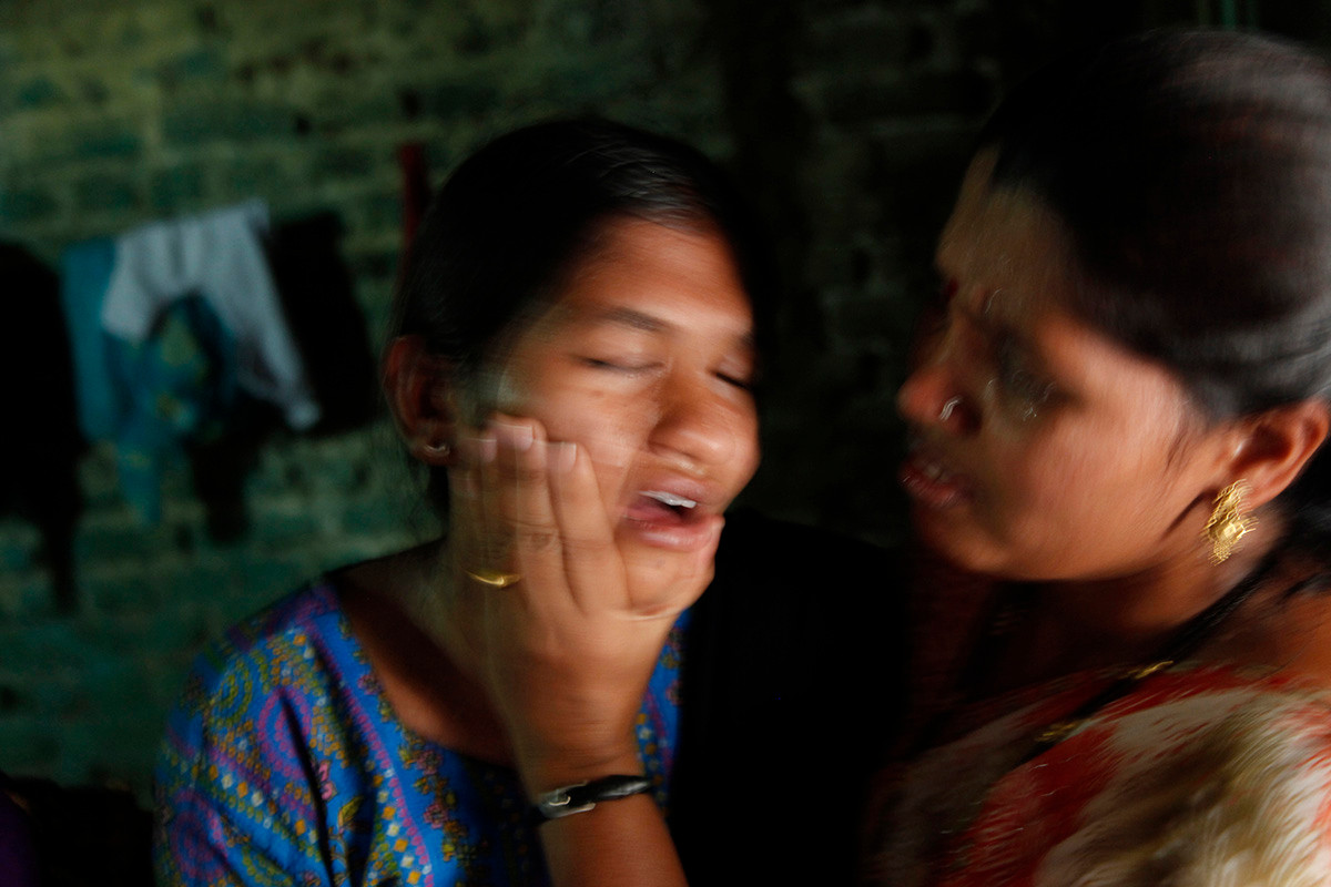 Pooja, the daughter of Vijay Thamke, a farmer from Sonbardi village who committed suicide, is consoled by a relative.