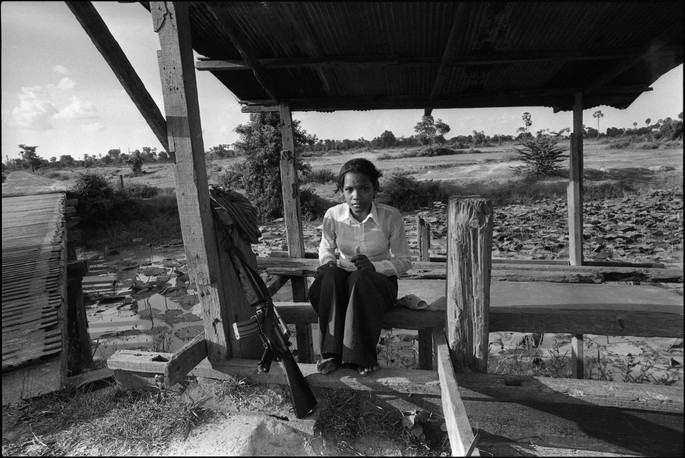 A teenage girl from a local militia guards a bridge in the countryside.