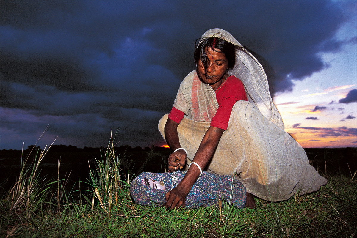 Katihar, Bihar. 1995: Phool Devi, a midwife, demonstrates how unwanted female infants are killed.