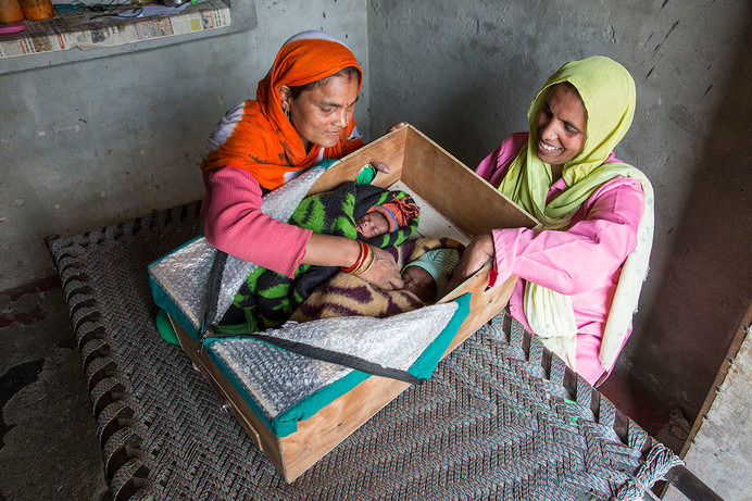 ASHA Poonam with Resham Rajkumar and her low-birth weight twins, Mansi and Manav, in a warm-box at their home in Mundet village, Haridwar district, Uttarakhand, India, 2018.