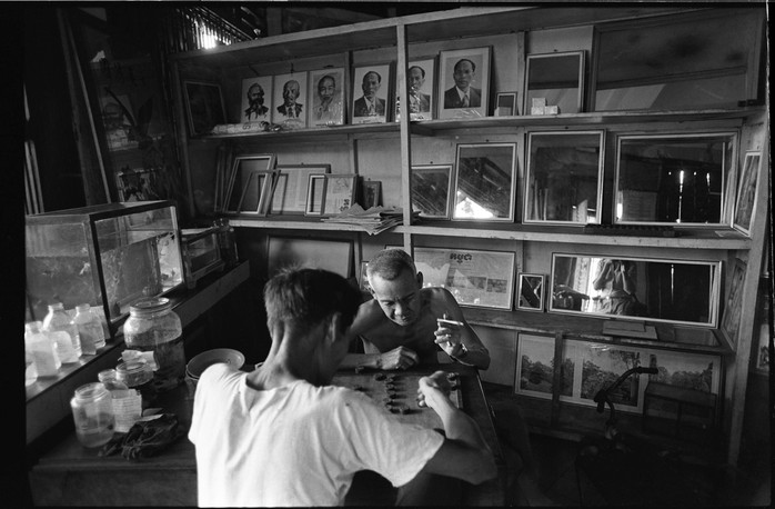 Two elederly men play a game of checkers in a shop in Phnom Penh.