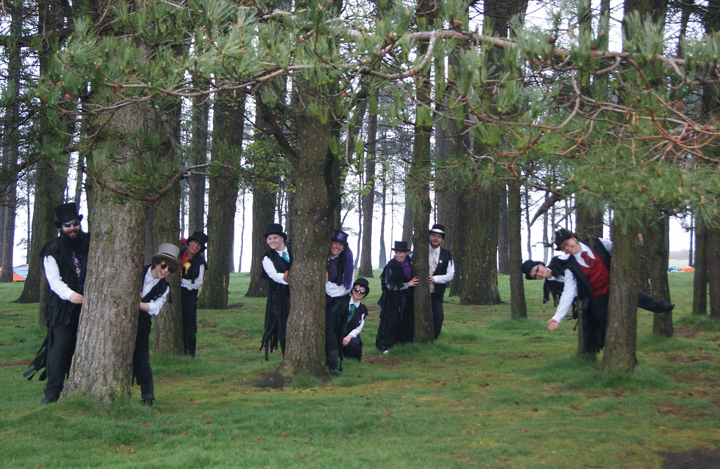 May Morning on May Hill. Te members ofThe Tattered Court peer out from amog the trees.