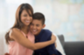 A happy and smiling Dolphin Kids™ parenting mom hugging her son after participating in a Dolphin Kids™ parenting workshop and program for parents and kids based on the Dolphin Kids™ parenting philosophy founded by Harvard-trained psychiatrist Dr. Shimi Kang.