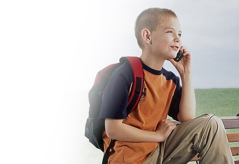 A young boy talking on a mobile phone