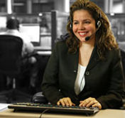 Smiling Relay Operator typing and looking at a monitor