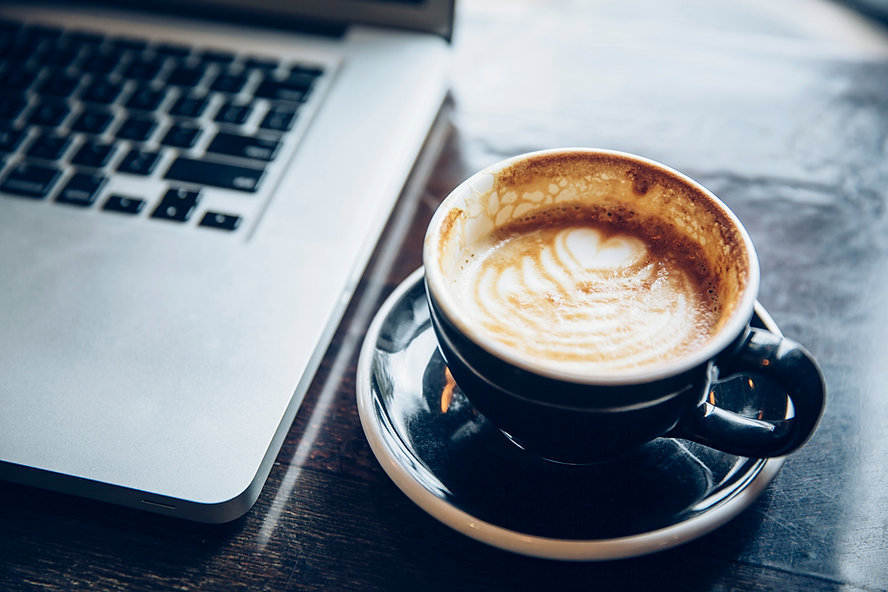 Image of a coffee cup next to a computer.