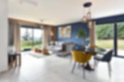 projet de rénovation en isere avec carrelage gris, mur bleu et beige, meuble sur mesure avec tasseaux de bois. tasseaux en lignes de bois pour encadrer la vue panoramique. mettre en valeur une grande pièce.