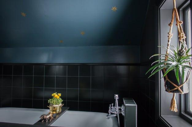 Salle d'eau bleu et noire, ciel étoilé doré plante suspendue par des cordages à la fenêtre noire. Baignoire avec tablette amovible, et crédence en carrelage noir. Villa Petula décrit par Tiffany Fayolle