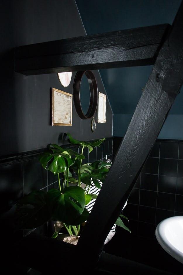 Intérieur sombre et élégant dans la pénombre, avec des murs noir et du carrelage noir, du sol au plafond la salle de bains est sombre avec des étoiles dorées, des cadres en dentelle traditionnelle, une vasque à poser, un miroir rond, des poutres noires apparentes, un projet trouve sur le site de VillaBetula et décrypter par Tiffany Fayolle architecte d'intérieur et décorateur à Lyon sur le blog