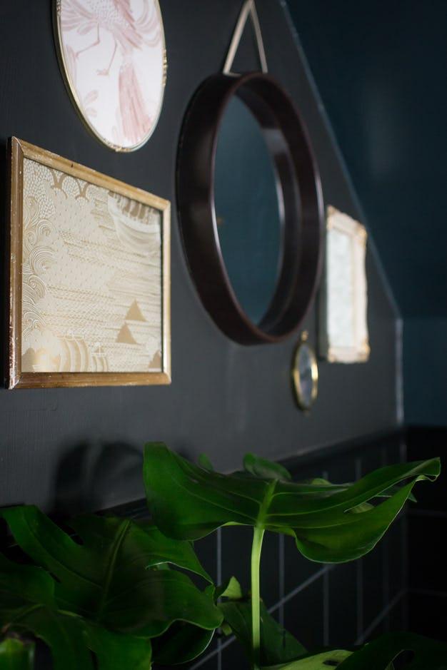 Decoration de salle de bains noire et sombre, avec une crédence noire et des plafonds bleus avec des etoiles dorees, tableaux en dentelle et miroir rond avec cadre en bois sombre, plante grasse type tropicale, un intérieur VillaPetula décrit par la décoratrice française Tiffany Fayolle.