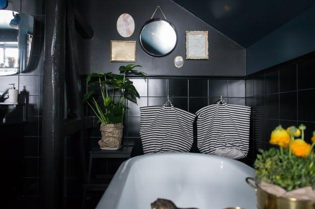 Salle de bains sombre dans les tons de noir au niveau du carrelage de la crédence, de la peinture noire également, des poutres et de la décoration. Un miroir rond et des tableaux en dentelle sont installés au dessus de la baignoire, des plantes grasses permettent d'apporter de la vie dans la pièce, un intérieur trouvé sur villapetula et expliqué dans le blog de Tiffany Fayolle architecte d'intérieur et décorateur à Lyon.