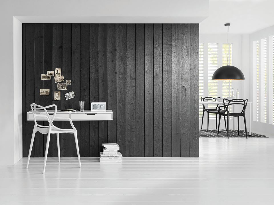 Revêtement mural en bois brulé noirci en lames verticales avec sol blanc et intérieur blanc épuré.