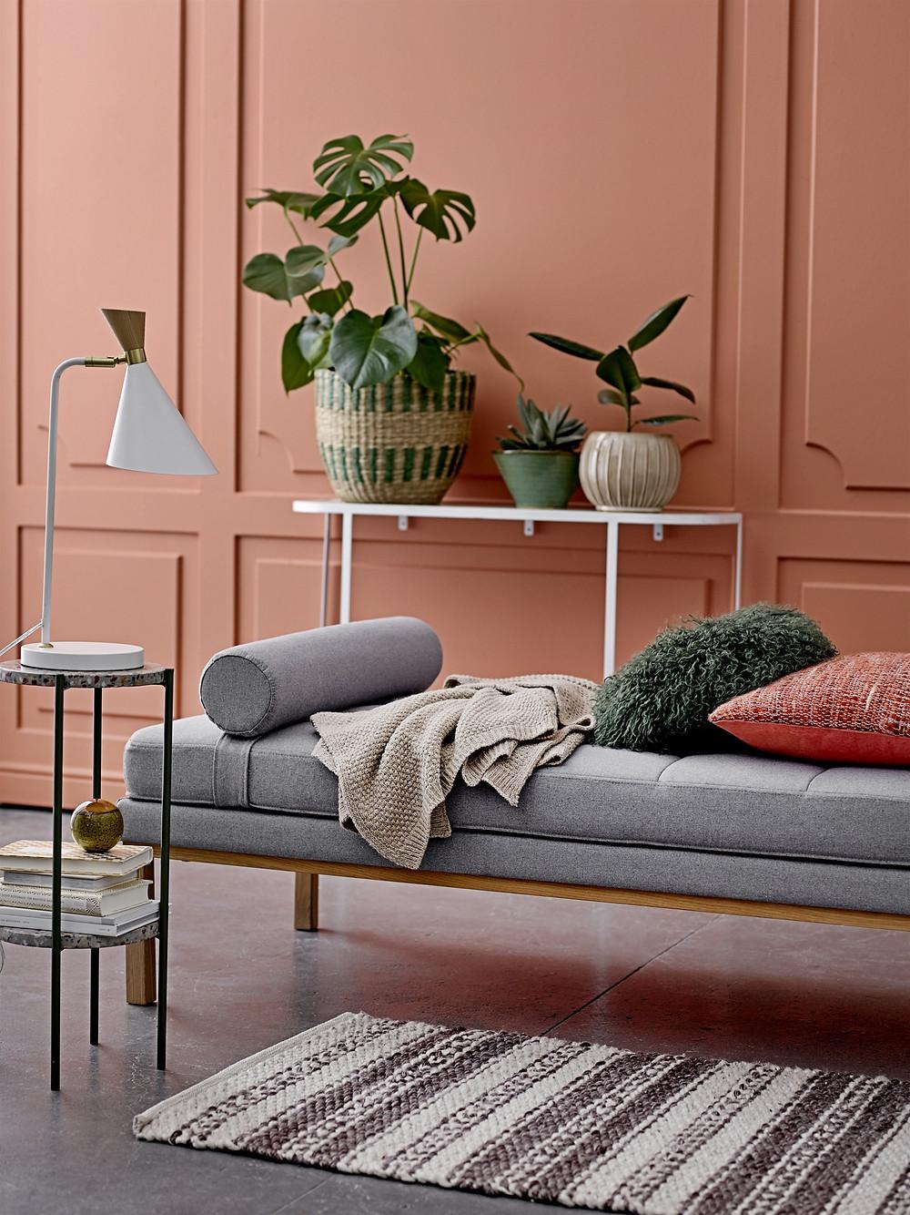 intérieur classique avec moulures entièrement revisité dans un style de couleurs pastel corail avec accessoires minimalistes