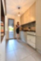 Dans cet cuisine amenagee par ses soins, tiffany fayolle architecte d interieur et decorateur a lyon pose en lisant un livre de cuisine peut etre d amenagement de cuisine. Un piano lacanche trône dans la cuisine equipee et renovee par l architecte d interieur et decoratrice lyonnaise avec les stratifiés gris souris de chez Egger et Cuir Brun de chez Egger et réalisés par le menuisier JEB agencement à Vienne e