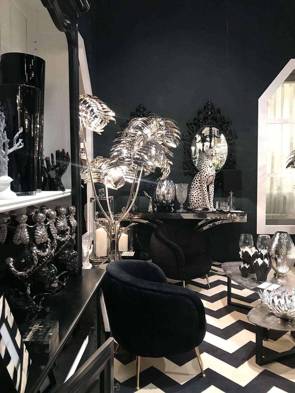 mur sombre, noir dans une ambiance élégante et luxueuse. Palmier de métal argenté.