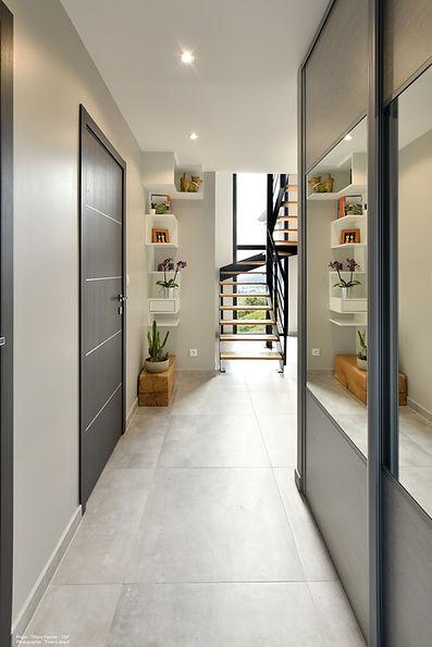 entrée et mobilier sur mesure caissns sur mesure asymétriques blancs. Carreaux gris et portes miroirs pour apporter plus e lumièr. Escalier métal et bois.