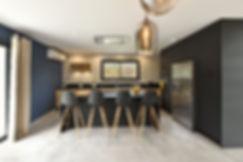 cuisine noire mat avec poignées et tabourets noirs et bois; Mur bleu velours mat farrow and ball et huisseries noires