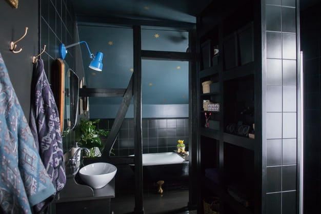 Salle de bains sombre dans les tons de bleu et de noir, avec des dorures, un vasque à poser en faïence sur un meuble laqué noir. Des poutres apparentes noires dans la baignoire, des carreaux noirs également, une inspiration VillaPetula et un article de Tiffany Fayolle blogueuse déco lyonnaise