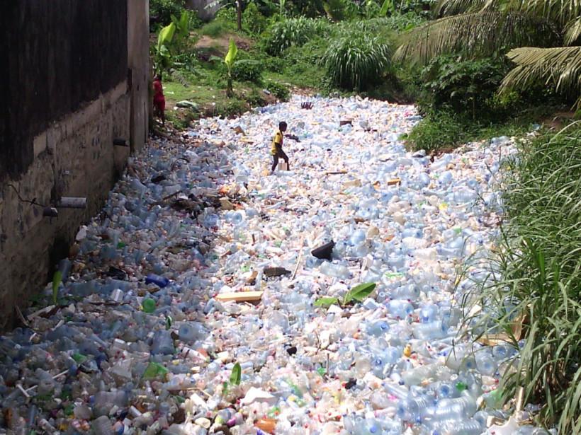 Des enfants jouent dans un drain obstrué par des bouteilles plastiques au quartier Madagascar à Douala. Crédit Photo: Mathias Mouendé Ngamo