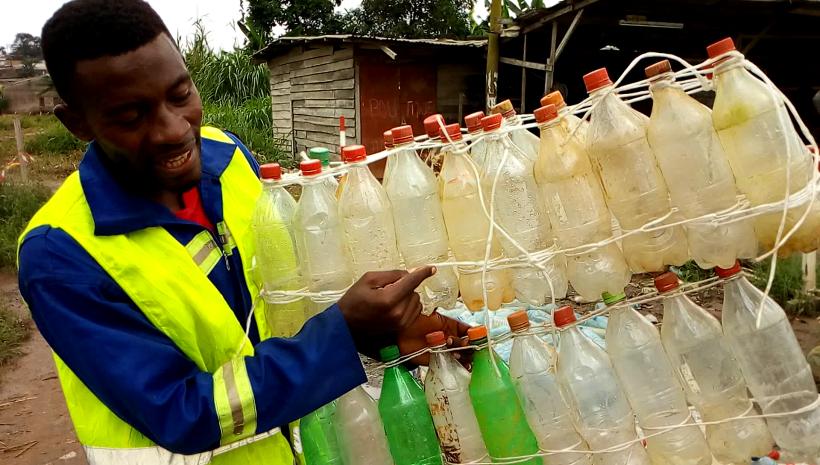 Ismaël Essome présente des blocs de bouteilles plastiques, base de la construction de la pirogue écologique. Crédit photo: Mathias Mouendé Ngamo