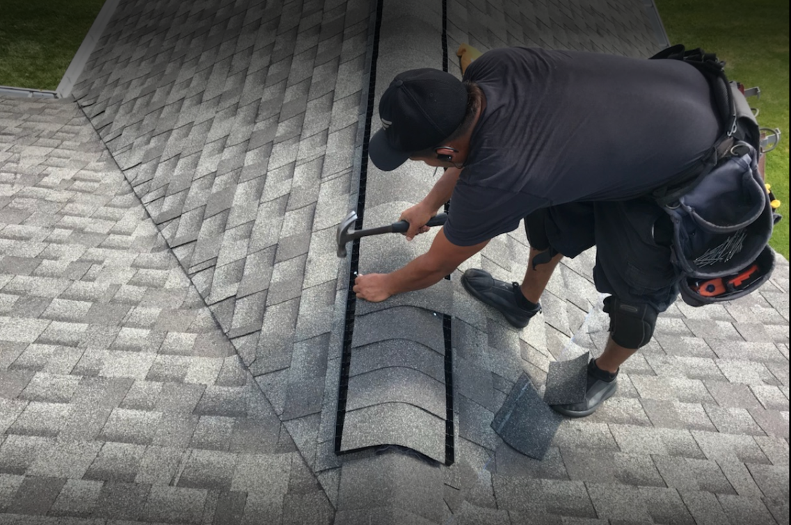 Manually hammering ridge cap shingles.pn