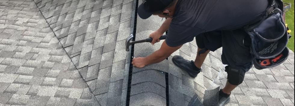 Manually hammering ridge cap shingles.pn