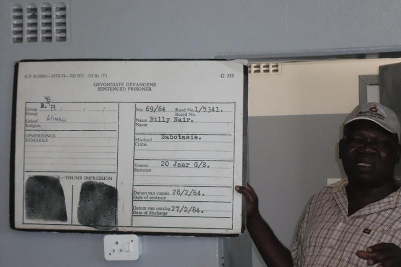 احد السجناء السياسين السابقين اثناء الجولة داخل السجن شديد الحراسة ويوضح لنا البطاقة التعريفية لأحد السجناء
