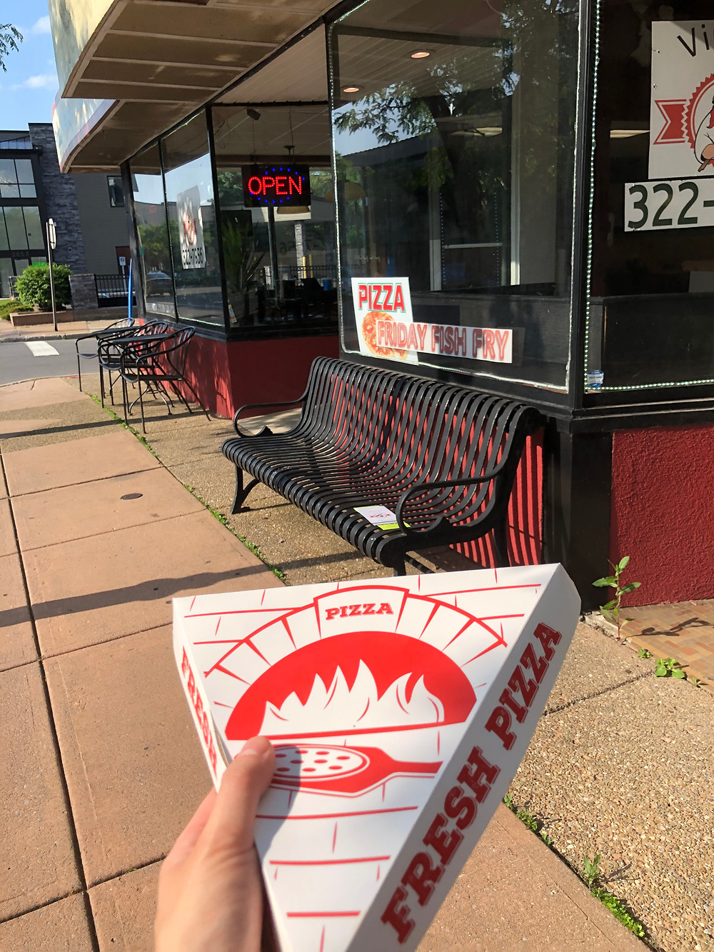 A hand holding a pizza slice box outside of Vinny's Pizzeria